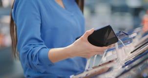 O close-up de uma mulher em uma loja da eletrônica que realiza em seu smartphone novo das mãos dois e escolhe a melhor uma posiçã video estoque