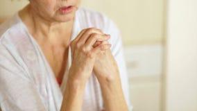 O close-up de uma mulher idosa com artrite mancha suas mãos com a pomada de cura Conceito da medicina e da farmacologia video estoque
