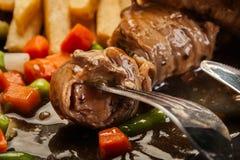 O close up de uma parte de rolos da carne de porco carregou na forquilha Foto de Stock Royalty Free