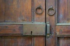 O close up de uma trava envelhecida de madeira e dois oxidaram aldravas de porta do anel sobre uma porta de madeira ornamentado fotos de stock royalty free