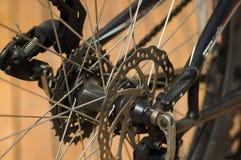 O close up detalhou o olhar em mecânicos de deslocamento da engrenagem da roda de bicicleta durante reparos da manutenção Fotos de Stock