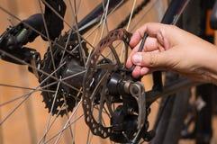 O close up detalhou o olhar em mecânicos de deslocamento da engrenagem da roda de bicicleta durante reparos da manutenção, mão us Foto de Stock Royalty Free