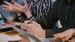 O close-up disparado, as mãos de executivos profissionais na grande tabela do escritório com café e os dispositivos cooperam n video estoque
