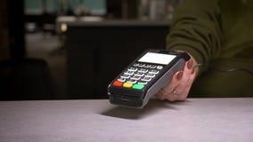 O close-up disparado da pessoa que usa o cartão do terminal e de crédito executa o pagamento sem contato e imprime a verificação filme