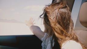 O close-up disparou da jovem mulher feliz com cabelo do voo e distribui da janela no carro que move-se rapidamente no deserto do  vídeos de arquivo