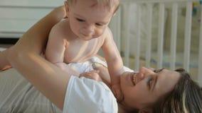 O close up disparou da mãe nova feliz que tem o divertimento com seu filho do bebê na cama no quarto filme