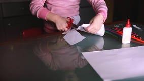 O close-up disparou da menina pré-escolar bonito em formas cor-de-rosa do corte da camiseta com as tesouras do papel, refletindo  filme