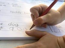 O close-up disparou das mãos da criança que escrevem no livro foto de stock royalty free