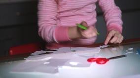 O close-up disparou das mãos prées-escolar da menina em formas cor-de-rosa do corte da camiseta do papel com tesouras e do desenh video estoque