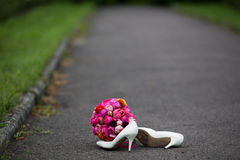 O close up disparou de sapatas brancas elegantes do casamento e de um ramalhete fresco Imagem de Stock Royalty Free