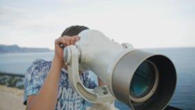 O close-up disparou do adolescente de quinze anos que olha a costa de mar no telescópio do elevado alto vídeos de arquivo
