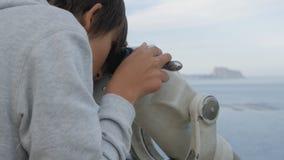 O close-up disparou do adolescente que olha o mar no telescópio da plataforma de observação elevado alta vídeos de arquivo