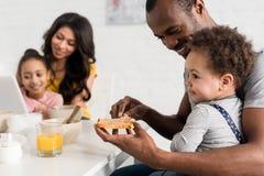 o close-up disparou do pai que aplica a manteiga de amendoim no brinde para o filho imagens de stock royalty free