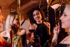 O close-up disparou dos amigos fêmeas bonitos positivos que aumentam vidros do vinho para o evento feliz que senta-se em elegante foto de stock
