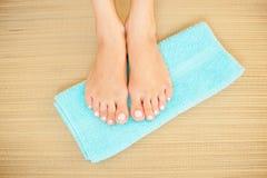 O close-up disparou dos pés bonitos da mulher com os pregos cor-de-rosa brilhantes na toalha azul Fotografia de Stock