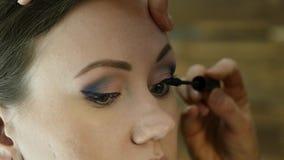 O close-up do artista de composição profissional tinge os olhos do modelo com uma grande escova cosméticos da indústria da moda filme