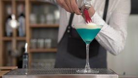 O close-up do barman novo considerável entrega a adição de um chantiliy ao cocktail colorido azul Terminação fazendo um azul filme