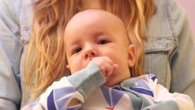 O close-up do bebê mastiga seus dedos ao sentar-se nas mãos no mum video estoque