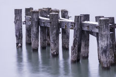 O close up do cais velho afixa quebrado e a posição na água calma, pequenina Imagens de Stock