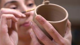 O close up do ceramist da mulher sublinha os detalhes que usam a borla no copo cru da argila em suas mãos filme