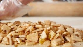 O close-up do cozinheiro chefe entrega a colocação da maçã à torta na cozinha do restaurante filme