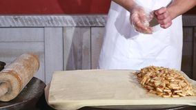 O close-up do cozinheiro chefe entrega a colocação da maçã à torta na cozinha do restaurante vídeos de arquivo