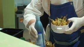O close-up do cozinheiro chefe entrega o cozimento e a preparação de peixes pequenos no restaurante vídeos de arquivo