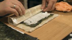 O close-up do cozinheiro chefe entrega o cozimento e a preparação do alimento e do sushi asiáticos na cozinha do restaurante filme