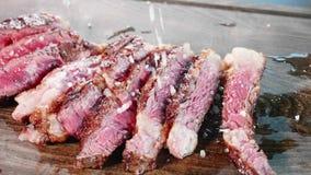 O close-up do cozinheiro chefe polvilha um grande sal no bife fritado desbastado da carne video estoque