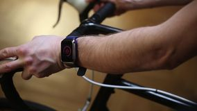 O close-up do desportista entrega dar certo na bicicleta dentro no gym video estoque