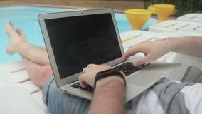 O close-up do freelancer masculino da piscina está trabalhando em um projeto para o portátil filme
