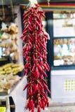 O close-up do grupo muito do vermelho coloriu pimentas com um fundo unfocused das tendas do alimento situadas no mercado chamado  Fotos de Stock Royalty Free