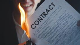 O close-up do homem de negócios queima um original do contrato em um fundo escuro O homem quebra um contrato em uma maneira extre filme