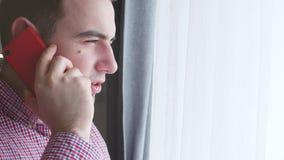 O close up do homem novo em uma camisa de manta fala em um telefone vermelho ao olhar para fora a janela 4K Fotage conservado em  filme