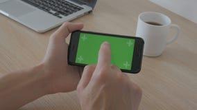 O close-up do homem realiza no smartphone das mãos com chave verde do croma da tela na tabela, no café e no portátil do local de  filme