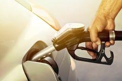 O close-up do homens entrega o reenchimento do carro com uma bomba de gás fotos de stock royalty free