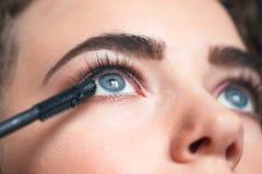 O close up do maquilhador que aplica o smokey eyes a composição Procedimento da extensão da pestana fotos de stock royalty free