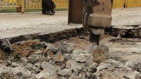 O close-up do martelo hidráulico do braço quebra o asfalto na estrada filme