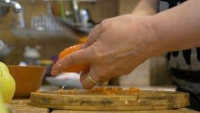 O close-up do meio envelheceu a mulher que descasca uma cenoura em casa na cozinha usando a receita tradicional para uma refeição video estoque