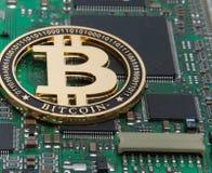 O close-up do ouro mordeu a moeda, a placa de circuito do computador com processador do bitcoin e os microchip Moeda eletrônica,  foto de stock