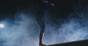 O close-up do pé de uma ginasta da menina executa um salto do feixe de equilíbrio no fumo e no movimento lento filme