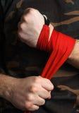 O close-up do pugilista da mão puxa envoltórios do pulso antes da luta Imagens de Stock Royalty Free