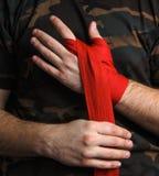O close-up do pugilista da mão puxa envoltórios do pulso antes da luta Imagem de Stock