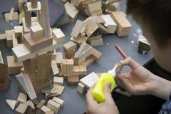 O close-up do ` s da criança entrega o jogo com construtor de madeira, tijolos na tabela O menino cola blocos para fazer a casa,  imagens de stock royalty free