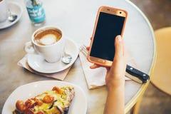 O close-up do ` s da mulher entrega guardar o telefone celular ao beber o café e ao comer a quiche vegetal no café moderno imagens de stock