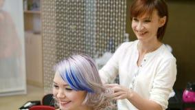 O close-up do ` s do cabeleireiro entrega usando a laca no cabelo do ` s do cliente no salão de beleza Cabelo da mulher da fixaçã filme