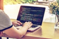 O close-up do ` s do programador entrega o trabalho em códigos fonte sobre um portátil em um dia ensolarado fotos de stock