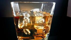O close-up do uísque de derramamento do empregado de bar no vidro bebendo com os cubos de gelo no fundo preto, época de relaxa a  vídeos de arquivo