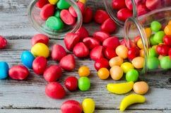O close-up doces vermelhos e amarelos de f dispersou dos frascos Fotos de Stock