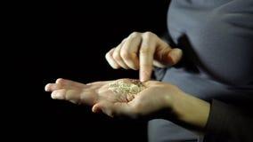 O close-up dos dedos move sementes de sésamo à disposição em um fundo preto filme